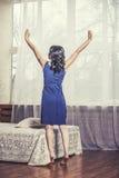 La bella donna fa una pausa il letto in mezzo di grande allungamento di Windows Immagine Stock