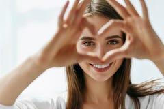 La bella donna felice che mostra il segno di amore vicino osserva Immagine Stock