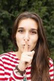 La bella donna felice ha messo l'indice alle labbra come segno di sile Fotografie Stock