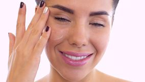 La bella donna idrata il fronte con crema video d archivio