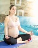La bella donna incinta che medita su stuoia al sole rays Immagine Stock Libera da Diritti