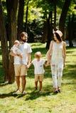 La bella donna indossa i vestiti e le passeggiate bianchi del cappello con il padre ed i bambini bei nel parco meraviglioso sulla fotografia stock