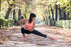 La bella donna ispanica di sport in abiti sportivi che allungano la flessibilità facente felice dopo sorridente del corpo si eser Fotografie Stock Libere da Diritti