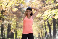La bella donna ispanica di sport in abiti sportivi che allungano la flessibilità facente felice dopo sorridente del corpo si eser fotografia stock