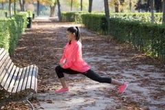La bella donna ispanica di sport in abiti sportivi che allungano la gamba sul banco che fa gli esercizi della flessibilità si sca Fotografie Stock