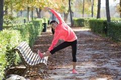 La bella donna ispanica di sport in abiti sportivi che allungano la gamba sul banco che fa gli esercizi della flessibilità si sca Immagini Stock Libere da Diritti