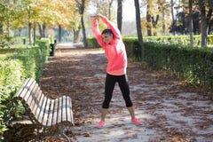 La bella donna ispanica di sport in abiti sportivi che allungano il corpo accanto al banco che fa gli esercizi della flessibilità Immagini Stock Libere da Diritti