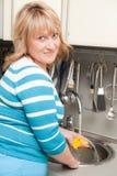 La bella donna lava i piatti Fotografie Stock