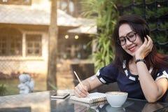 La bella donna lavoratrice scrive sul taccuino circa l'affare immagine stock