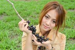 La bella donna mangia la frutta nella sosta Fotografie Stock Libere da Diritti
