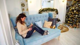 La bella donna moderna si siede su Internet e sui rotoli sulle notizie della compressa, sedentesi sul sofà blu nella stanza festi archivi video