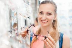 La bella donna nel deposito dell'ottico sceglie i suoi vetri immagine stock libera da diritti