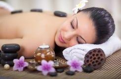 La bella donna nel salone della stazione termale con le pietre calde dentro appoggia Fotografia Stock