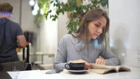 La bella donna passa il suo tempo in un caffè: lettura del libro e bere caffè