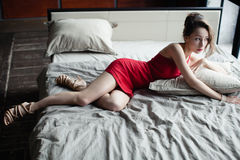 La bella donna in poco vestito rosso si trova sul letto Immagine Stock Libera da Diritti