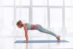 La bella donna pratica il asana Chaturanga Dandasana - posa limbed di yoga del personale quattro allo studio di yoga immagini stock