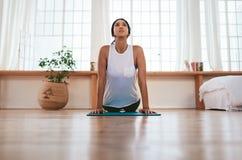 La bella donna pratica il asana di yoga a casa Fotografie Stock