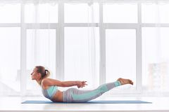 La bella donna pratica il asana Salabhasana - posa di yoga della locusta allo studio di yoga fotografia stock
