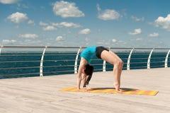 La bella donna pratica l'yoga sul mare immagine stock