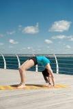 La bella donna pratica l'yoga sul mare fotografia stock