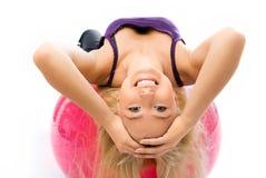 La bella donna risolve sulla sfera di forma fisica fotografie stock