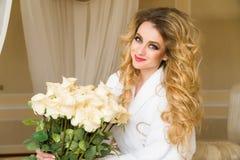 La bella donna seducente che flirta con la macchina fotografica sta sedendosi sul letto con un grande mazzo delle rose bianche ne Immagini Stock Libere da Diritti