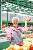 La bella donna senior che indossa i vetri vende il pepe su marke fotografia stock libera da diritti