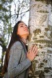 La bella donna si è appoggiata una betulla che guarda il cielo Fotografie Stock