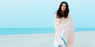 la bella donna si è avvolta con la coperta sulla spiaggia Fotografia Stock