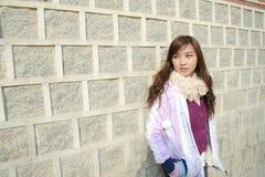 La bella donna si distende l'azione contro la parete Fotografie Stock Libere da Diritti