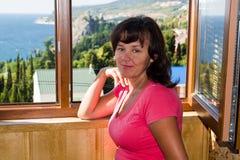 La bella donna si leva in piedi prima di una finestra Fotografia Stock