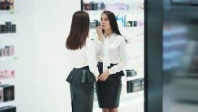 La bella donna si pavoneggia davanti allo specchio in deposito cosmetico
