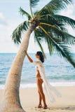 La bella donna si rilassa sulla spiaggia sabbiosa tropicale sul fondo della palma fotografia stock