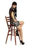 La bella donna si siede sull'alta presidenza di legno. Fotografia Stock Libera da Diritti