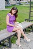 la bella donna si siede in una sosta su un banco Fotografie Stock Libere da Diritti