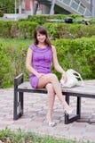 La bella donna si siede in una sosta su un banco Immagine Stock Libera da Diritti