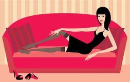 La bella donna si trova su un sofà. vettore royalty illustrazione gratis