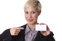 La bella donna sorride con un biglietto da visita in bianco. Immagine Stock Libera da Diritti