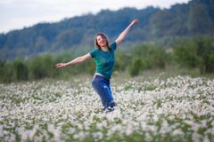 La bella donna sorridente felice sul campo della camomilla sta camminando sotto pioggia, tempo di molla Fotografia Stock