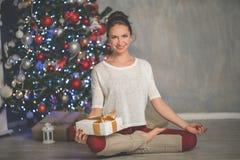 La bella donna sorridente flessibile con il contenitore di regalo sta facendo allungando l'albero a casa vicino decorato di natal Fotografia Stock