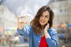 La bella, donna sorridente prende un'immagine se stessa con uno smartp Fotografia Stock