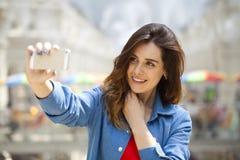 La bella, donna sorridente prende un'immagine se stessa con uno smartp Fotografia Stock Libera da Diritti
