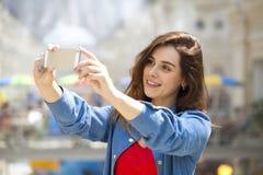 La bella, donna sorridente prende un'immagine se stessa con uno smartp Fotografie Stock