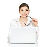 La donna si siede dalla tavola del thÑ con il computer portatile in camicia bianca Fotografia Stock