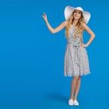 La bella donna sorridente in vestito e cappello punteggiati di Sun sta indicando Fotografia Stock