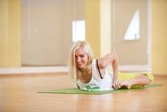La bella donna sportiva degli Yogi di misura pratica il asana Bhekasana - posa di yoga della rana nella stanza di forma fisica Immagini Stock