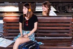 La bella donna sta aspettando il suo amico sul banco di legno ed ascolta fotografia stock libera da diritti