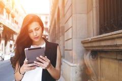 La bella donna sta leggendo il messaggio di testo sul cuscinetto di tocco mentre sta stando sulla via nel giorno di primavera Fotografia Stock Libera da Diritti