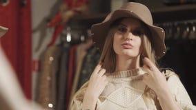 La bella donna sta mettendo sulla sua testa un cappello di feltro in un deposito prima dello specchio stock footage