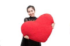 La bella donna sta mostrando il cuscino e sorridere del cuore Fotografia Stock